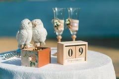 Épouser la table décorée avec le calendrier en bois de cube, verres de champagne, hiboux en céramique Image stock