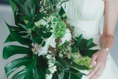 Épouser le bouquet nuptiale avec de grandes feuilles tropicales de vert et fleurs blanches Photographie stock