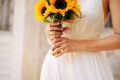 Épouser le bouquet nuptiale des tournesols dans les mains de la jeune mariée Photo libre de droits