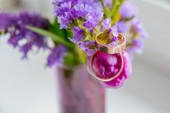 Épouser le concept : bouquet de rose, de tulipes pourpres et de deux anneaux d'or Branche fleurissante avec les fleurs pourpres e photographie stock libre de droits