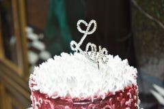 Épouser le gâteau blanc rouge sur une table avec l'écrimage Photographie stock