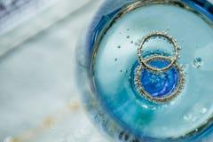 Épouser les anneaux d'or en verre de champagne Photographie stock