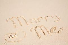 Épousez-moi écrit sur le sable Photos stock