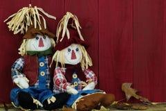 Épouvantails de garçon et de fille se reposant par la grange en bois rouge antique Image libre de droits