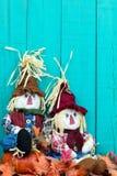 Épouvantails se reposant par le décor de chute par la barrière en bois bleue de sarcelle d'hiver Photographie stock