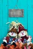 Épouvantails se reposant sous le signe vide par le décor de feuillage d'automne Photographie stock