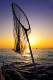 Épuisette dans la pêche de bateau sur l'eau de mer de lever de soleil Photo stock