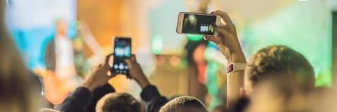 Épuisez l'enregistrement mobile avancé, les concerts d'amusement et le bel éclairage, image franche de foule au concert de rock,  image libre de droits