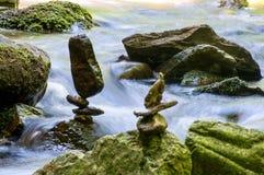 Équilibrage en pierre par la rivière image stock