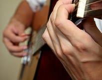 A équipé des mains jouant la guitare Images stock