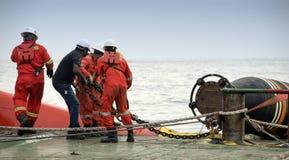 Équipage marin faisant l'opération de connexion de tuyau image libre de droits
