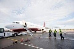 Équipage se penchant sur l'avion de While Standing By de barrière photographie stock
