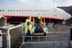 Équipage travaillant au convoyeur de bagage fixé à l'avion image stock