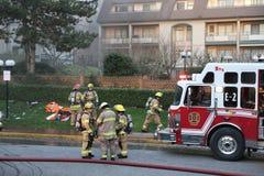 Équipages de sapeur-pompier luttant le feu de complexe d'appartements Photos libres de droits