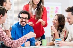 Équipe à l'agence créative discutant lors de la réunion Image stock