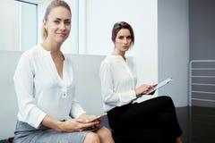 Équipe élégante de deux femelles tenant le comprimé numérique et le téléphone portable tandis qu'entrevue commençante de attente, Photographie stock