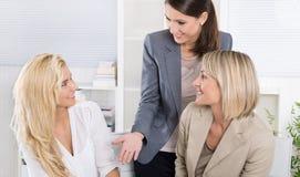 Équipe : Équipe réussie d'affaires de femme dans le bureau parlant à Photographie stock