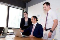 Équipe américaine d'affaires de personnes ayant utilisant l'ordinateur portable pendant une réunion et les présents photos libres de droits