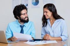 Équipe arabe riante d'affaires au travail au bureau photos stock