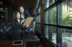 Équipe asiatique d'affaires discutant le document au café photos stock