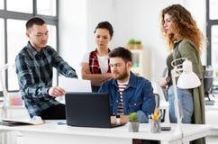 Équipe créative avec l'ordinateur portable fonctionnant au bureau images stock