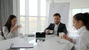 Équipe créative buvant les boissons chaudes de la tasse sur le bureau blanc et spacieux de fond, café-coupure dans le bureau, clips vidéos