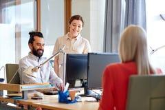 Équipe créative heureuse avec des ordinateurs dans le bureau Images stock