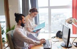 Équipe créative heureuse avec l'ordinateur dans le bureau Image stock