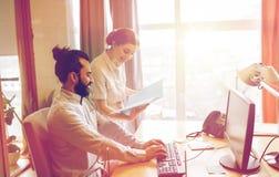 Équipe créative heureuse avec l'ordinateur dans le bureau Image libre de droits