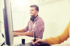 Équipe créative heureuse avec l'ordinateur et le comprimé de stylo Image libre de droits