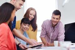 Équipe créative heureuse avec le PC de comprimé au bureau Image stock