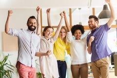 Équipe créative heureuse célébrant la victoire dans le bureau Photo stock