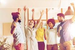 Équipe créative heureuse célébrant la victoire dans le bureau Photographie stock