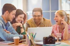 Équipe créative heureuse d'affaires utilisant l'ordinateur portable lors de la réunion photo stock