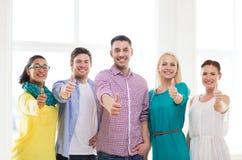 Équipe créative heureuse montrant des pouces dans le bureau Image stock