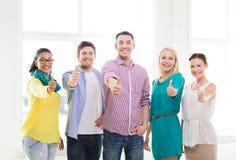 Équipe créative heureuse montrant des pouces dans le bureau Image libre de droits