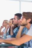Équipe créative s'asseyant dans une ligne écoutant quelque chose Photographie stock libre de droits