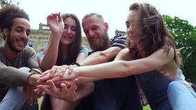 Équipe d'étudiants joyeux pliant des mains ensemble clips vidéos