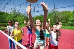 Équipe d'adolescents jouant le volleyball sur la cour Photos libres de droits