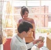 Équipe d'affaires à la maison vérifiant des actions dans des affaires à la maison en ligne images stock