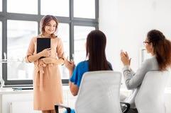 Équipe d'affaires applaudissant à la femme au bureau Photographie stock