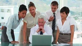 Équipe d'affaires autour de leur patron regardant un écran d'ordinateur portable banque de vidéos