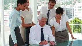 Équipe d'affaires autour de leurs whos de patron écrivant sur un dossier clips vidéos