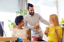 Équipe d'affaires avec des tasses de café parlant au bureau Images libres de droits