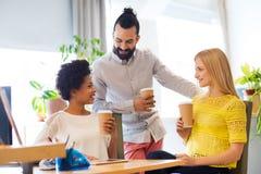 Équipe d'affaires avec des tasses de café parlant au bureau Photos stock