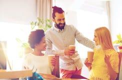 Équipe d'affaires avec des tasses de café parlant au bureau Image stock