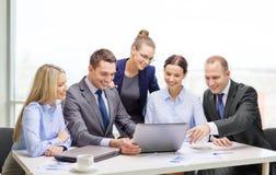 Équipe d'affaires avec l'ordinateur portable ayant la discussion Image libre de droits