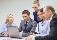 Équipe d'affaires avec l'ordinateur portable ayant la discussion Images stock