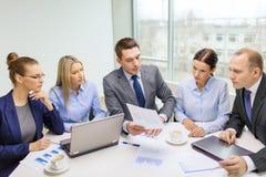 Équipe d'affaires avec l'ordinateur portable ayant la discussion Photographie stock libre de droits