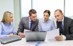 Équipe d'affaires avec l'ordinateur portable ayant la discussion Image stock